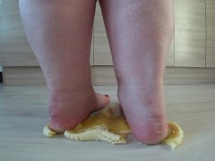 a big mature woman, bbw, smash a banana with bare feet, heels. crash trampl