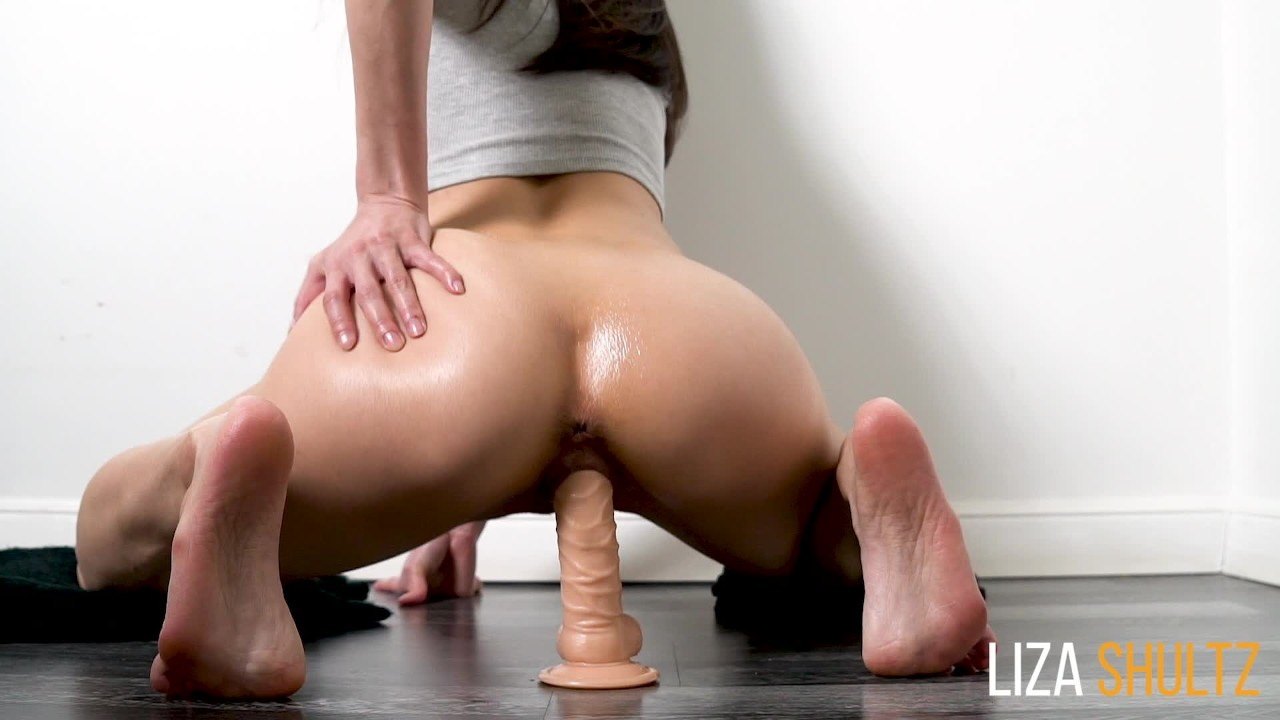 Young girl in oil shows legs and rides a dildo.