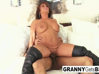 Mature takes the black cock in her bed